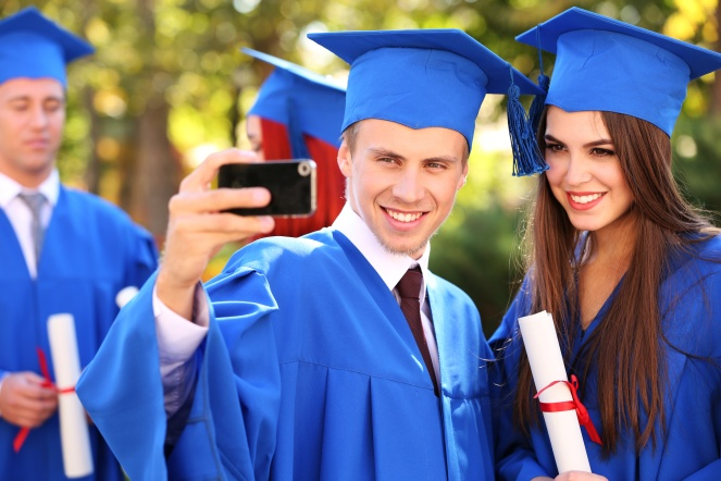 Graduate students wearing graduation hat and gown, outdoors, Taking a Selfie